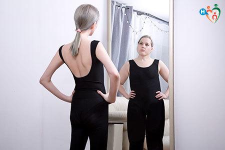 Ragazza bulimica si guarda allo specchio