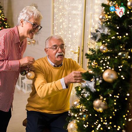 Due persone anziane addobbano l'albero di Natale