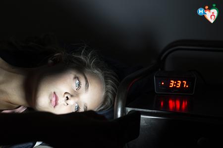 Immagine che ritrae una ragazza insonne a letto