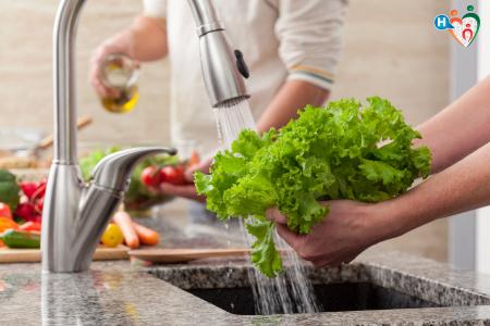Fotografia che raffigura verdure lavate sotto l'acqua corrente secondo le norme ISS