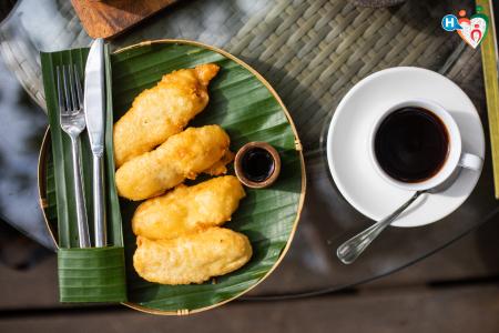 Fotografia che ritrae un piatto con alimenti fritti e caffè
