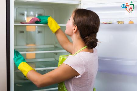 Fotografia di una donna che sbrina e pulisce il frigo