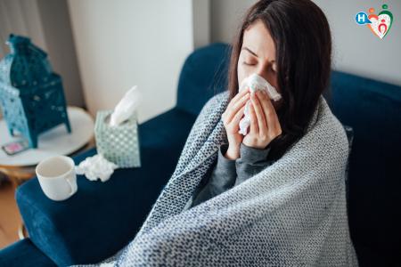 Fotografia di una donna sul divano che si soffia il naso