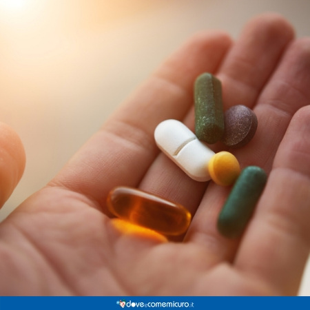 Immagine che raffigura una mano con integratori e pillole