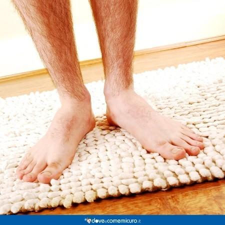 Immagine che ritrae dei piedi bagnati sul tappetino del bagno