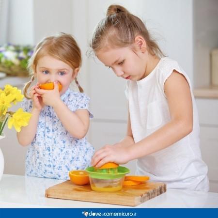 Immagine che ritrae due bambine che spremono arance