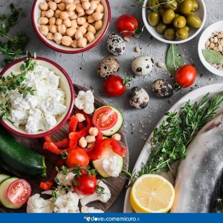 Immagine di una tavola con ceci, uova, pesce azzurro, zucchine, formaggio e pomodori