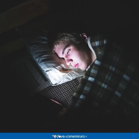 Immagine che ritrae un ragazzo a letto mentre guarda il telefono