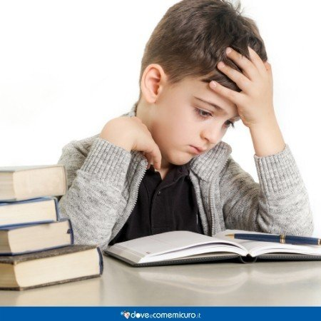 Immagine che ritrae un bambino che fatica sui libri