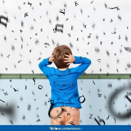 Immagine di un bambino circondato da lettere che lo perseguitano