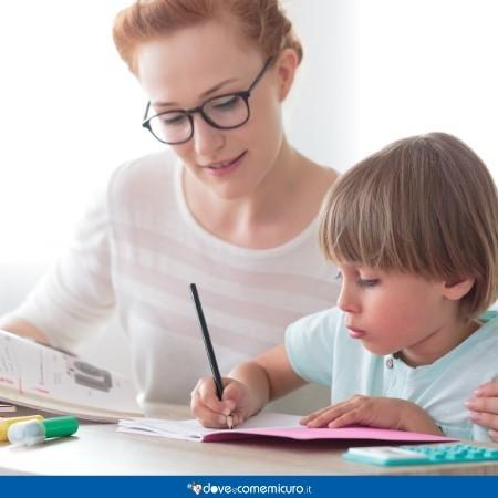 Immagine di una maestra che supporta un bambino mentre studia