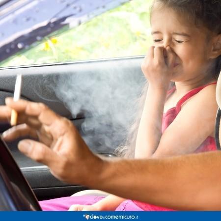 Immagine di una bambina soggetta al fumo passivo in auto del padre
