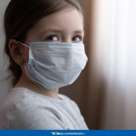 Immagine che ritrae una bambina con la mascherina in ospedale
