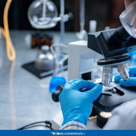 Immagine che ritrae un professionista al microscopio in laboratorio