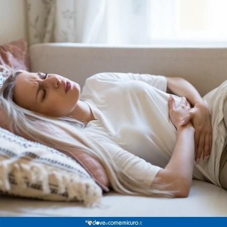 Fotografia di una ragazza che si tiene la pancia per il dolore mestruale