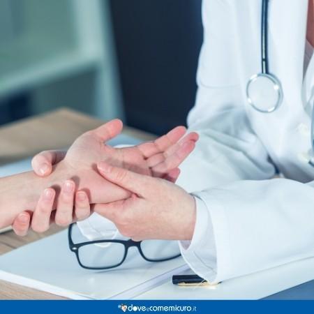 Immagine di un dottore che visita le mani di una paziente