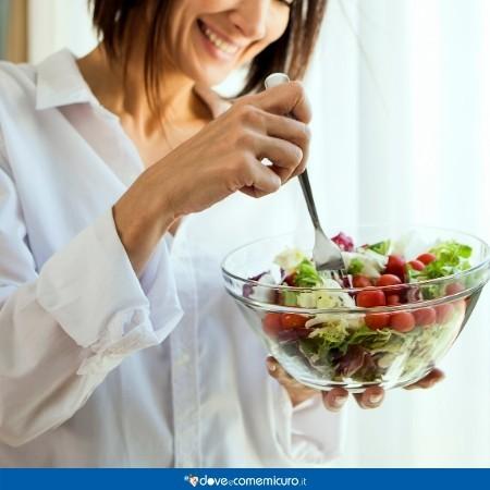 Fotografia di una donna sorridente in cucina che mangia verdura