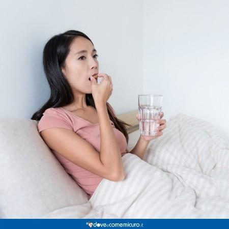 Immagine di una ragazza che assume la pillola del giorno dopo a letto