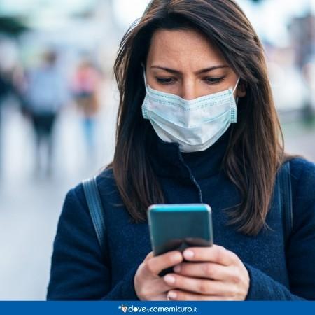 Immagine di una donna che tiene in mano lo smartphone mentre indossa la mascherina