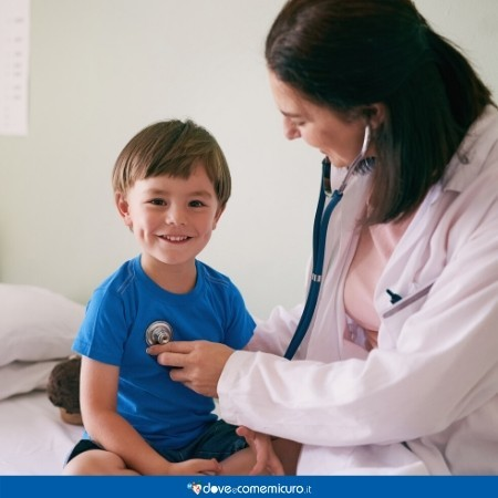 Immagine che mostra una dottoressa mentre ausculta un bambino