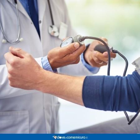 Immagine di un medico che misura la pressione arteriosa a un paziente