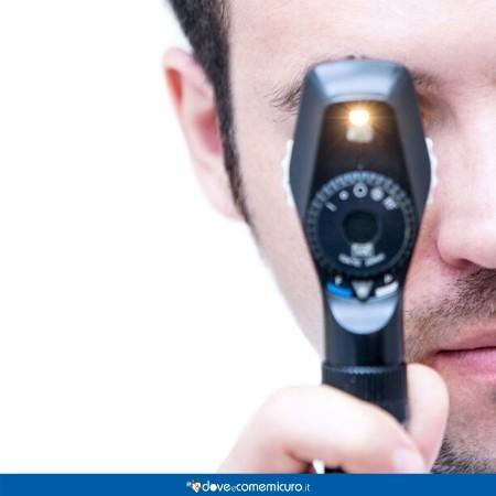 Immagine che ritrae un oculista che procede a visitare un paziente