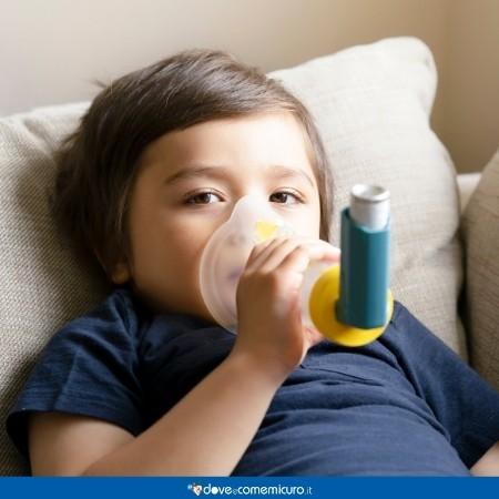 Immagine di un bambino sdraiato a letto che respira grazie a una mascherina perché ammalato di asma