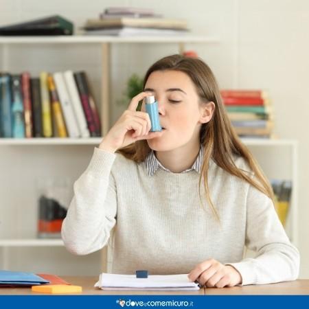 immagine di una ragazza con l'asma seduta a un tavolo mentre studia e fa i compiti