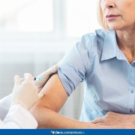 Immagine che mostra una donna di mezza età mentre si vaccina