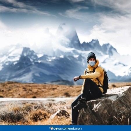 Immagine che mostra un ragazzo in montagna per fare trekking con la mascherina