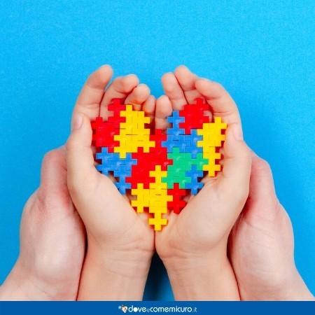 Immagine che raffigura due mani che tengono un puzzle colorato