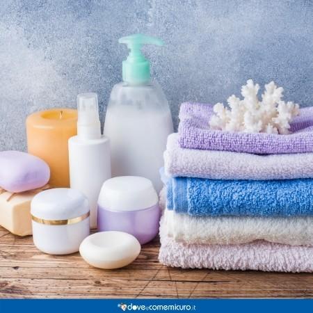 Immagine che ritrae asciugamani e saponi appoggiati sopra una mensola di legno del bagno