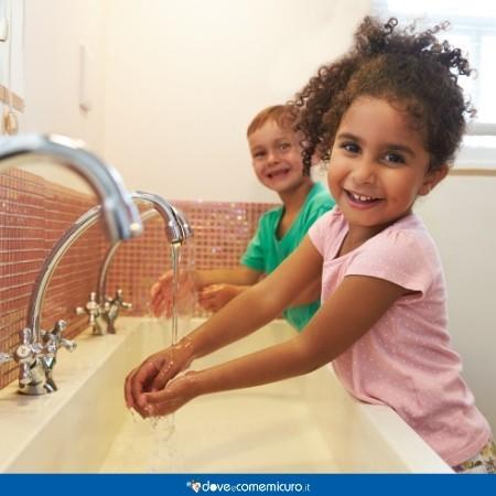 Fotografia che ritrae dei bambini nell'atto di lavarsi le mani