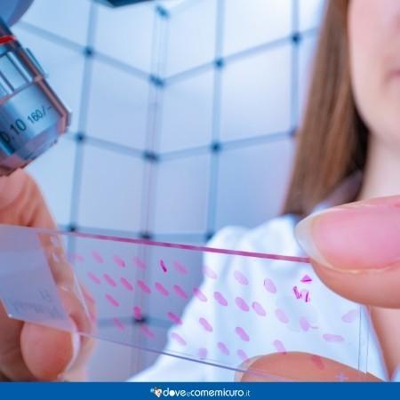 immagine con infermiera che guarda al microscopio dei campioni
