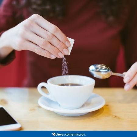 Immagine che ritrae una ragazza che mette il contenuto di una bustina di zucchero nel caffè