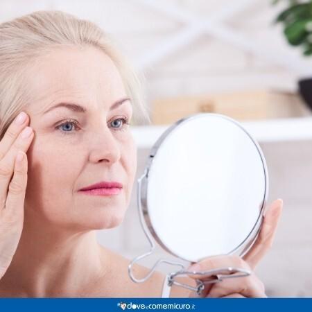 Immagine che mostra una donna di mezza età guardarsi allo specchio