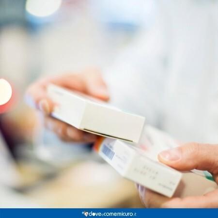 Immagine che mostra due scatole di farmaci tra le mani di un farmacista