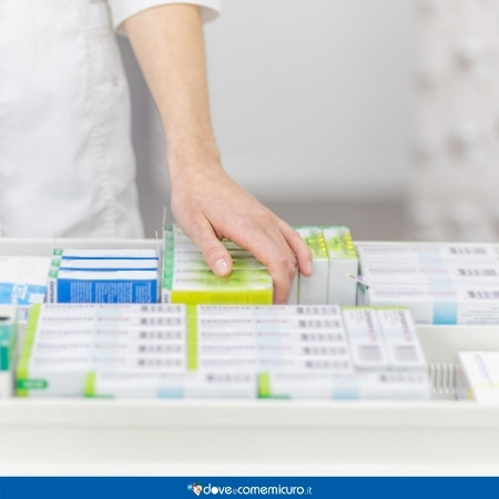 Immagine che mostra un farmacista mentre sceglie un farmaco dal cassetto