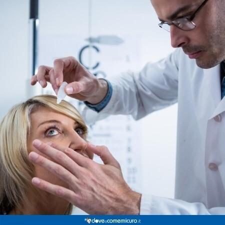Immagine che mostra una donna con congiuntivite che mette il collirio dall'oculista