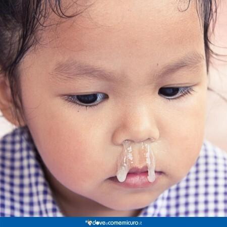 Immagine che mostra un bambino col naso che cola e un muco bianco trasparente