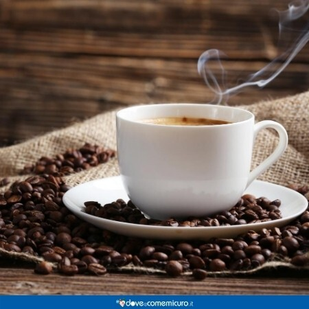 Immagine che mostra una tazzina di caffè sui chicchi di coffea arabica