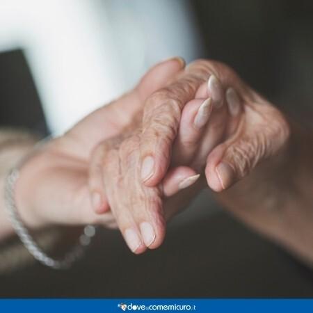 Immagine che mostra una mano di anziano tra quelle di un suo caro
