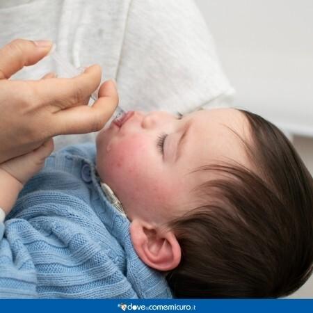 Immagine di un neonato mentre riceve una medicina attraverso una siringa