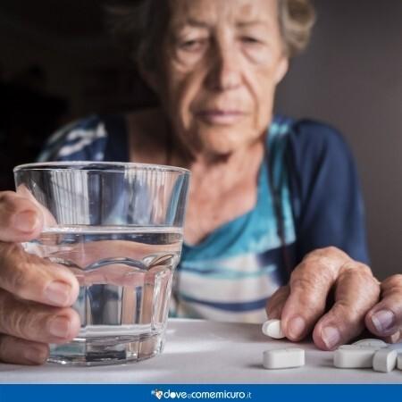 Immagine di un'anziana donna mentre prende delle pillole