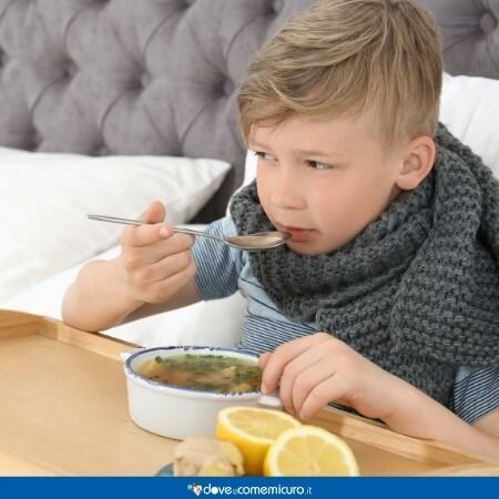L'immagine mostra un bambino a letto, malato, mentre mangia il brodo