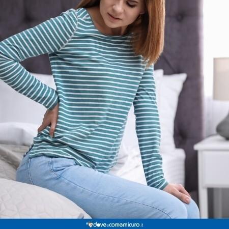 Immagine di una ragazza seduta sul letto che si tiene una mano sulla schiena dolorante