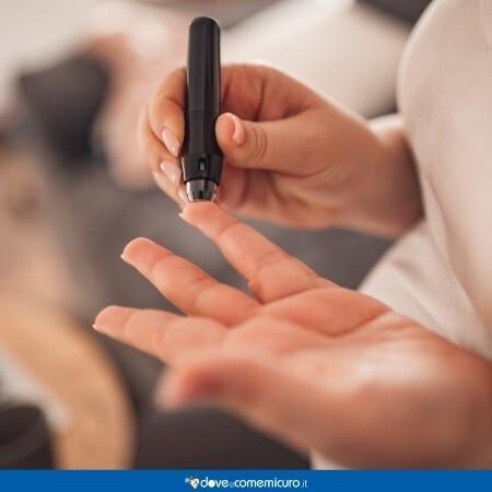 Fotografia che ritrae una mano che misura la glicemia con un dispositivo per diabetici