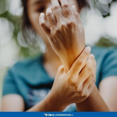 Immagine che mostra una donna che si tiene il polso dolorante