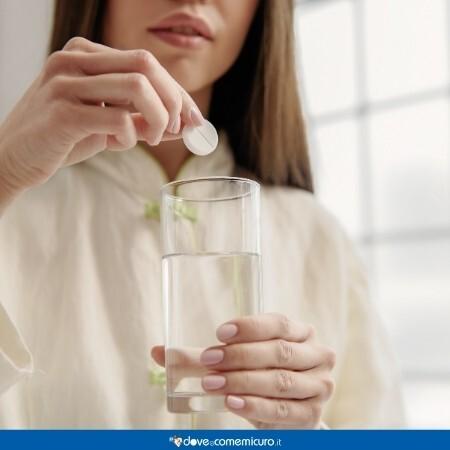 Immagine che mostra una ragazza che sta per prendere un'aspirina