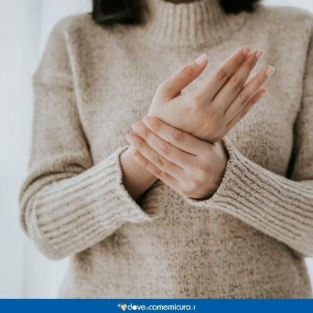 Immagine che mostra una ragazza che si tiene la mano dolorante